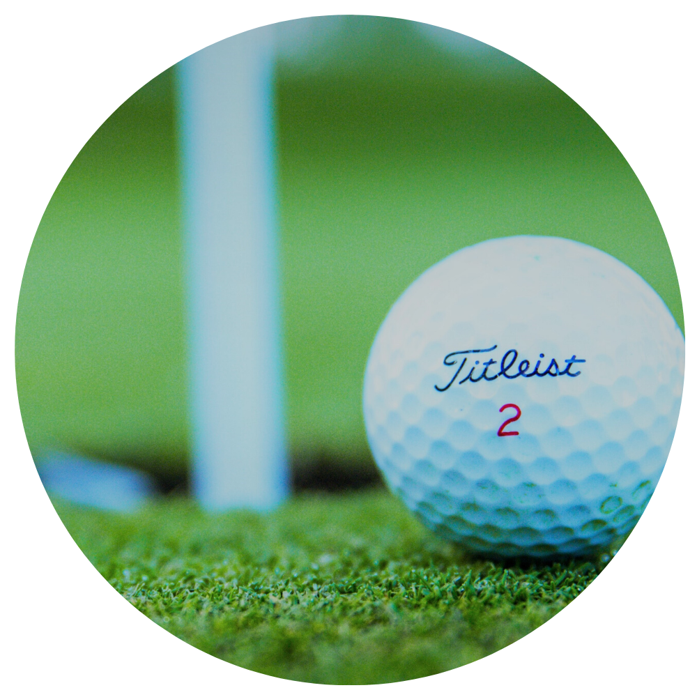 close up of a golf ball with blurred grass hole and golf flag in background