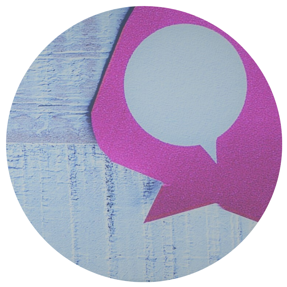 white wood table with pink paper chat bubble icon